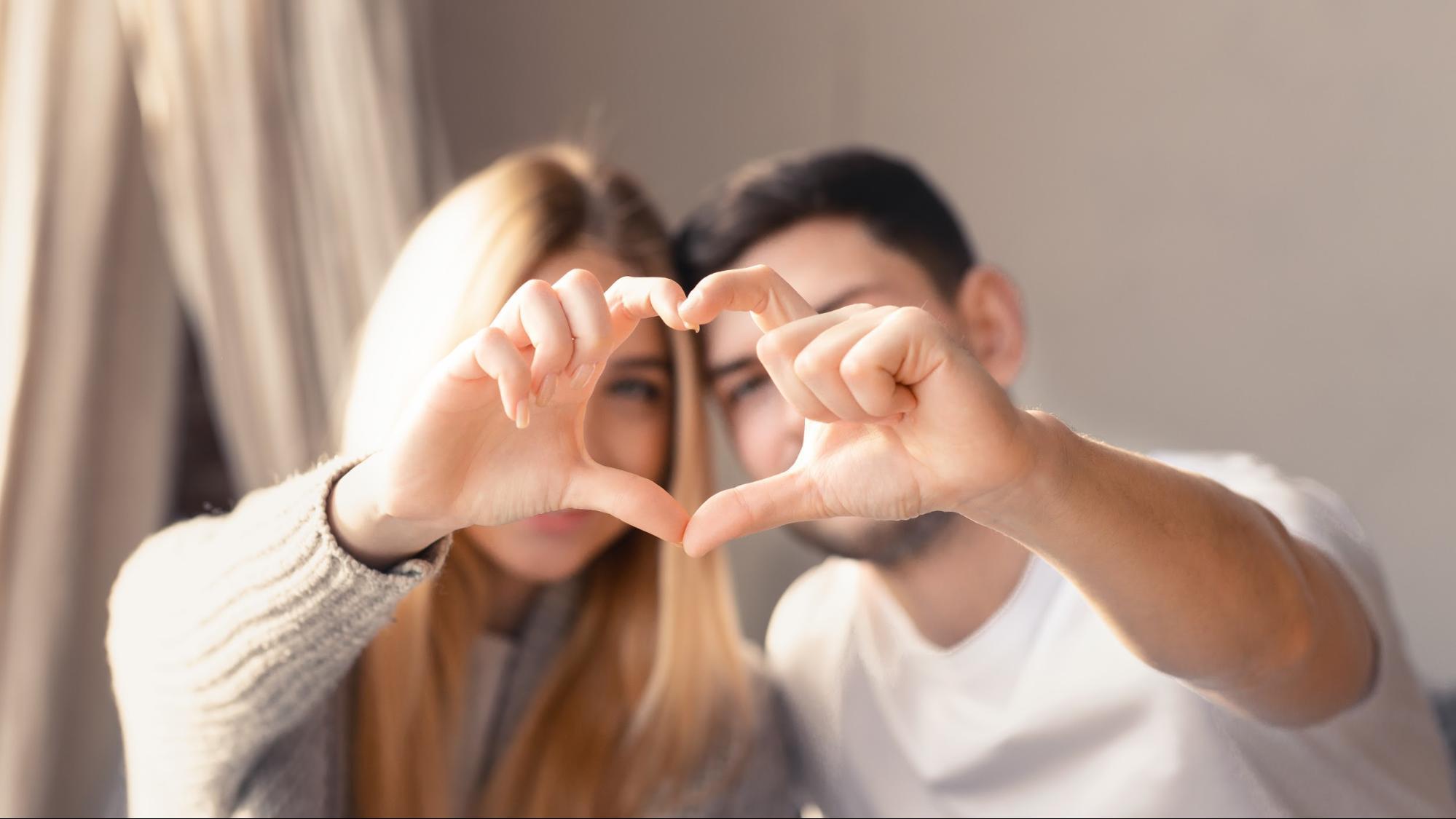 手でハートを作るカップルの写真
